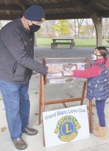 Natalia Salinas helps Lion Joe Bogar with the drawing at Turkeys in the Park. Courtesy photo