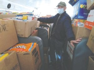 Jerry Bennett, FISH volunteer, helps collect more than 10,000 pounds of food and personal care items for local families Saturday at Grand Blanc High School. Photo by Lania Rocha