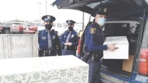 Michigan State Police Troopers Nicole Dhooghe, Katelyn Hammond and Steven Kramer load Thanksgiving food donations for Genesee County families at the Grand Blanc Kroger. Photo by Lania Rocha
