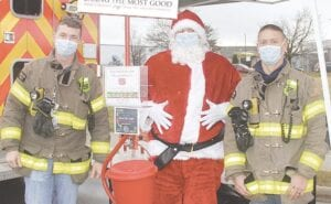From left, Burton Firefighters Jeremy Scharrer, Jacob Palmer (as Santa) and Cody Revolt were at Walmart in Burton on Saturday accepting toy donations for the Salvation Army. Photos by Gary Gould