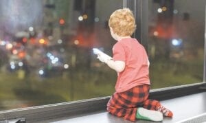 Jackson Pope, 3, watches the parade of first responder vehicles from his window at Hurley Children's Hospital, where he is a patient. Photos courtesy Doug Pike