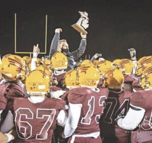The Davison Cardinals Varsity Football Team is shown here hoisting Coach Jake Weingartz up while he holds the district championship trophy, Nov. 13. File photo