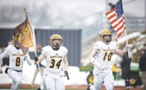 Payton Pizzala (34) and Harrison Unger (10) ran onto the field as the Cardinals were introduced carrying an American flag and a Davison Cardinals flag.