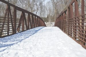 Although the Riverview Trail accumulates snow and ice, it is still well-traveled by residents during the winter months, especially over the Riverview Bridge section pictured here. Photo by Ben Gagnon