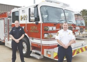 Sgt. Brett Beckley (left) and Assistant Fire Chief Mark Rowley (right) pose with the Flint Township Fire Department's newest fire truck. Photo by Gen Ganon