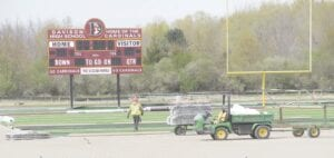 Work crews were laying the artificial turf at Cardinal Stadium, Monday. Work at the stadium should be completed by the end of May. Photo by Gary Gould