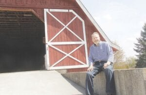 Bob Applegate sits in front of the two-story barn he and his father built in the 1990s.