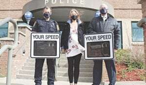 (left to right): Flint Township Resource Officer John Chisa, Hougen Foundation administrator Holly Hougen and Flint Township Police Chief Kevin Salter display the department's new radar speed signs. Photo provided