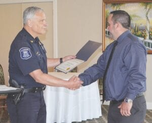 Officer Erick Eckles (right) received a Professional Excellence Award from Chief Hoonstra. Photo by Ben Gagnon