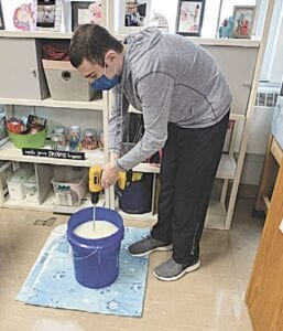 Reese, a Transitions class student, mixes soap for the program's laundry detergent products. Photos provided