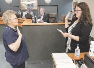 Deb Walton, left, is sworn in Monday night by Burton City Clerk Racheal Boggs. Photo provided