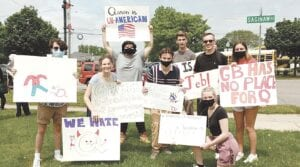 Grand Blanc High School students hold up signs during the demonstration opposing school board member Amy Facchinello and Q-Anon. Photo by Lania Rocha