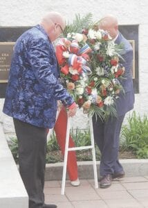 Burton City Council Vice President Greg Fenner, left, Mayor Duane Haskins, right, and Councilwoman Tina Conley (not pictured) place a wreath at the city's Veterans Memorial.