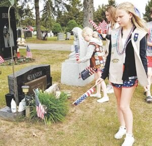 Paisley Roney, Raeleigh Genovesi and Payton Roney search for the graves of veterans at Evergreen Cemetery in Grand Blanc Township. Photo by Lania Rocha