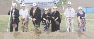 Members of the Davison Board of Education turning over dirt at the groundbreaking Monday for the new Davison High School Performing Arts Center. From left, Granger Stefanko, Eric Lieske, Matthew Smith, Karen Conover, Diane Rhines, Nick Goyette and Stephanie Thomas. Photo by Gary Gould