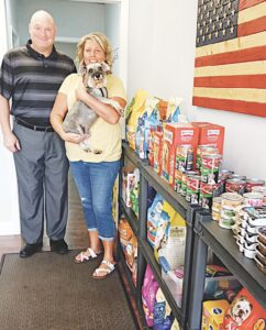 Tom and Kim Farrell, pictured with their schnauzer Miggy, maintain a pet pantry at Crown Real Estate in Carriage Plaza. The couple loves animals and wanted to give back to the community. Photo by Lania Rocha