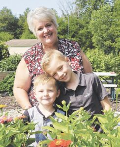 Dawn Raymond and her grandsons Wesley and Grayson Schaibly are responsible for stocking the farm stand with goods from the farm. Photo by Krystal Moralee