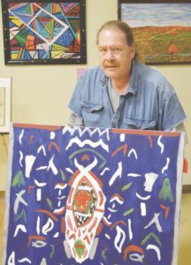 Matt Nelson, a Vista Center client and staff aide, shows off one of his paintings that's displayed at the Vista Visions Art Gallery. Photo by Ben Gagnon
