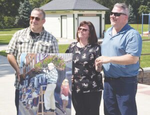 Lois Nickel, along with Gary Nickel's sons Steve Nickel (left) and Chris Nickel (right), accepted a commemorative painting of Gary from the Flushing Chamber of Commerce.