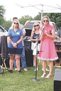 Grand Blanc Chamber President Leigh LaForest, left, and Amber Taylor, executive director of Back to the Bricks, right, greet the crowd at Roll On In.