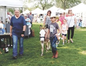 Pedro the miniature donkey leads the children's parade through the art fair grounds. Photo by Lania Rocha