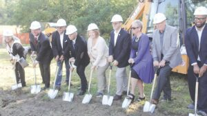 The ceremonial groundbreaking for the 240-foot water tower at 3036 S. Center Rd. in Burton. From left: Tina Conley, Burton City Council; Burton Mayor Duane Haskins; Chris Flores, district director for Congressman Dan Kildee; Jeff Wright, Genesee County Drain Commissioner; Genesee County Commissioner Ellen Ellenburg; State Rep. John Cherry; Barbara Baker-Omerod, Genesee County Water & Waste Advisory Board; State Rep. David Martin; and Gary Jones, from the office of Gov. Gretchen Whitmer. Photo by Gary Gould