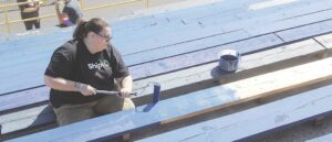 Volunteers spent Sunday morning and afternoon painting the bleachers and railings at the Bendle football stadium.