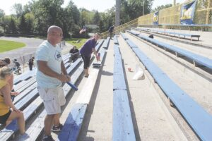 Burton Mayor Duane Haskins and Burton Clerk Racheal Ervin-Boggs at work painting bleachers at the Bendle stadium. Photos by Gary Gould