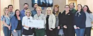 ELGA CU associates and CEO Karen Church present $20,000 check to Catholic Charities of Shiawassee and Genesee Counties President & CEO, Vicky Schultz. Photo provided